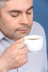 Happy adult man drinking coffee on blue.