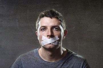 attractive man mouth sealed on tape freedom of speech concept
