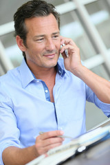 Middle-aged businessman talking on smartphone