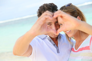 Romantic couple at the beach making heart sign with hands