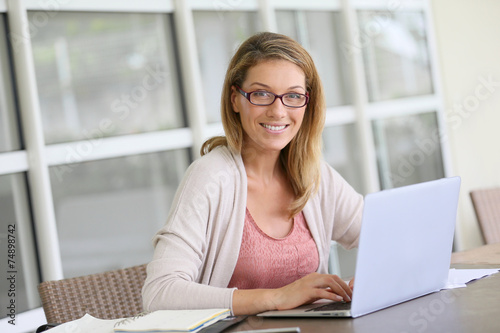 canvas print picture Middle-aged woman working from home on laptop