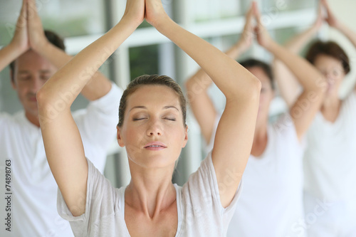 Papiers peints Zen Attractive blond woman attending yoga course with group