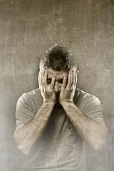 man suffering depression headache migraine  covering face