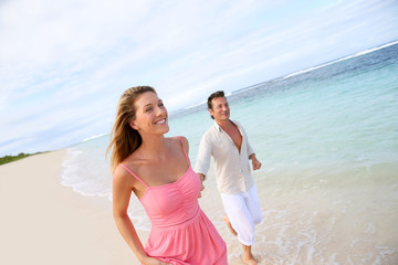 Romantic couple running on a sandy beach