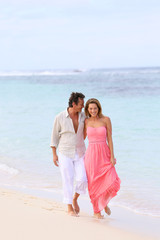 Romantic couple walking on a sandy beach