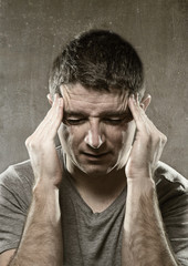 man suffering migraine headache in desperate pain feeling sick