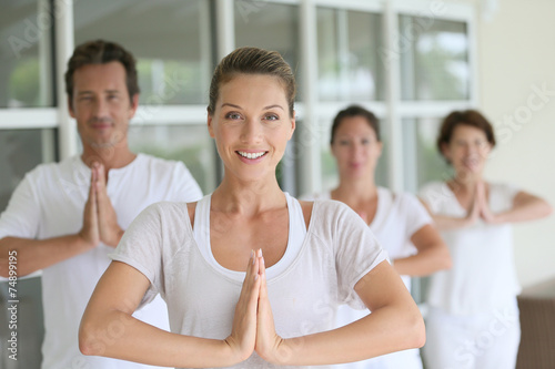 Foto op Canvas Zen Attractive blond woman attending yoga course with group