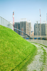 Walking path with green grass and construction site
