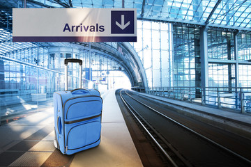 Arrivals. Blue suitcase at the railway station