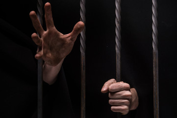 closeup on hands of man sitting in jail