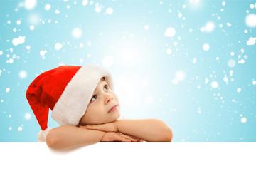 Little boy in Santa hat peeking from behind blank sign billboard