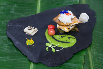 Fried fillet of white fish and vegetables on a black stone