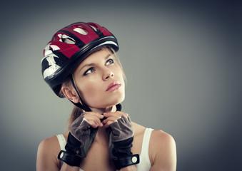 Cycling. Female putting biking helmet before ride.