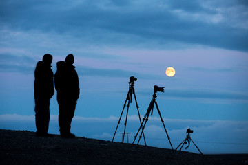 Backlit of photographers with tripod and cameras on full moon