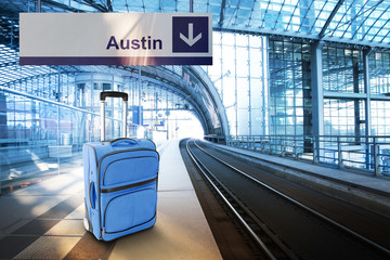 Departure for Austin. Blue suitcase at the railway station