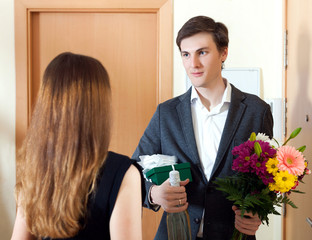 Man present bunch of flowers to his young wife