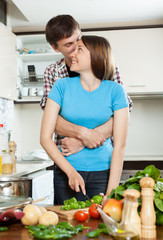 Young loving man and girl having flirt at domestic kitchen