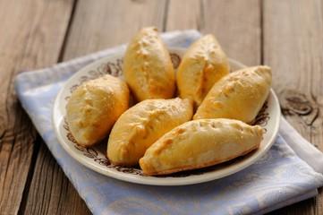 Russian pirogi, small pies on blue linen