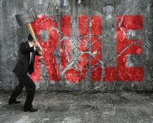 businessman using sledgehammer cracking red rule word broken