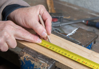 a worker measuring a board with a tape measure