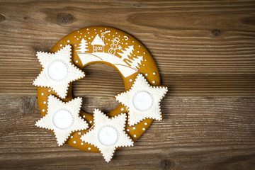 Gingerbread stars with candle on wooden backgrounds