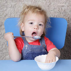 small child learns to eat with a spoon