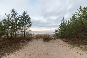 baltic beach in fall with clouds and waves towards deserted dune