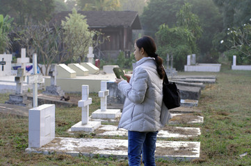 girl holding bible at cemetery