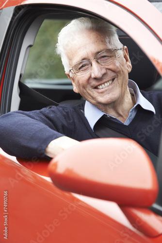 Leinwanddruck Bild Portrait Of Smiling Senior Man Driving Car