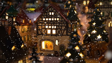 Small winter village scene with illuminated houses and snowing