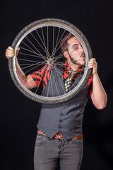 Young man blowing on bike wheel