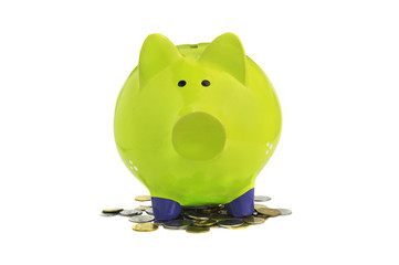 green piggy bank standing on coins isolated over white