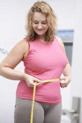 Happy Plus Size Woman Measuring Waist In Bathroom