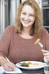 Woman On Diet Writing Details In Food Journal