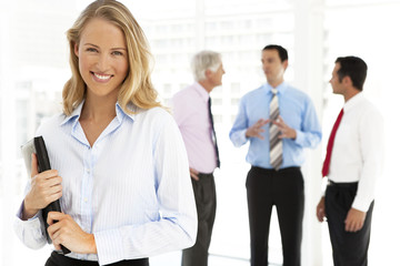 Portrait of a young businesswoman with partners on background