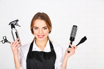 Beautiful girl hairdresser on light background