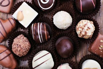 Many chocolates on wooden textured background