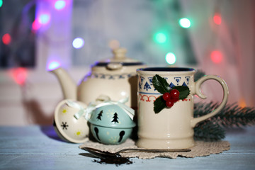 Christmas composition with cup and teapot of hot drink,