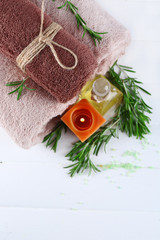 Branches of rosemary and sea salt, towels, candle and bottle