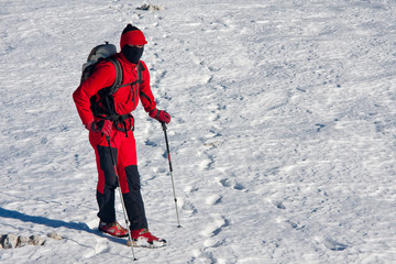 Mountaineer with balaclava dressed in red in red on the snow
