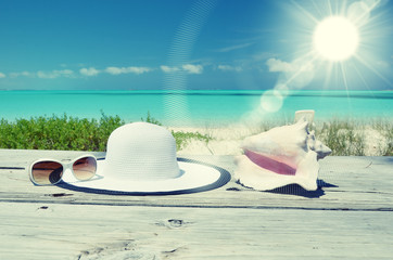 Sun glasses and hat against tropical beach of Great Exuma island