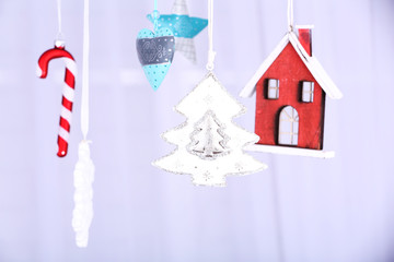 Hanging beautiful Christmas decorations on light background