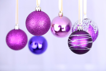 Hanging purple Christmas toys on light background