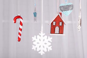 Hanging beautiful Christmas decorations on light background