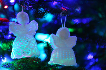 Knitted Christmas angels on Christmas lights background