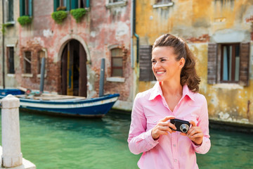 Happy young woman with photo camera looking on copy space