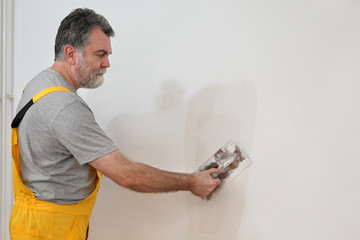 Worker repairing plaster at wall with trowel
