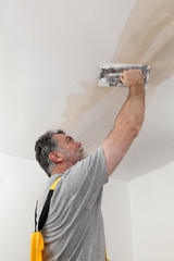Worker, mason repairing plaster at ceiling with trowel
