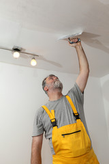 Worker repairing plaster at ceiling with trowel