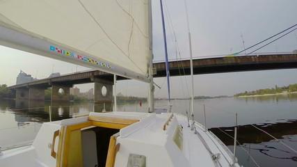 Yacht sailing under river city bridge, cityscape, pollution, POV